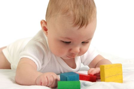 Baby playing with colorful wooden blocks.