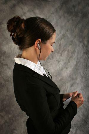 hands free phone: Mujer joven usando el receptor de cabeza de las manos libremente para el tel�fono port�til y tomando notas.