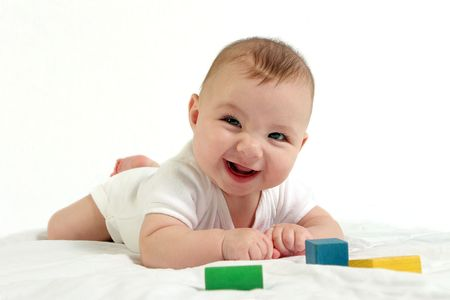 yellow block: Happy baby smiling at camera, playing with blocks Stock Photo
