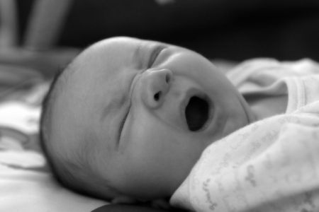 Baby yawning in black and white. Фото со стока