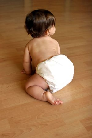 warm cloth: brown-haired caucasian baby wearing a cloth diaper, crawling away from camera.
