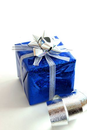 High-key image of a package in blue wrapping with silver trim Фото со стока