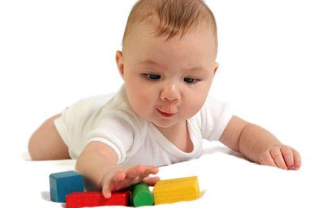 カラフルな木製のブロックに達する赤ちゃん