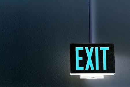 exit sign: lit exit sign hanging from the ceiling