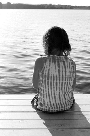 black and white image of a girl sitting on a pier, overlooking a lake Фото со стока