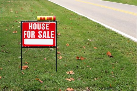 House for sale sign in grass by a road.