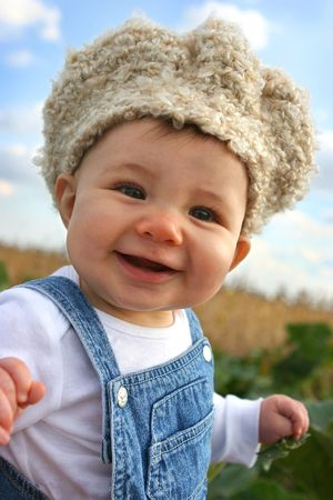 baby in overalls and crocheted hat