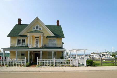 Yellow Victorian-style house with green roof. Blue sky and marina with sailboats in background.