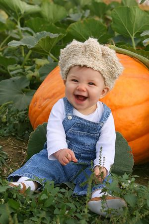 laughing baby sitting with a pumpkin