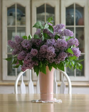 Vase of lilacs on a wooden farm table.