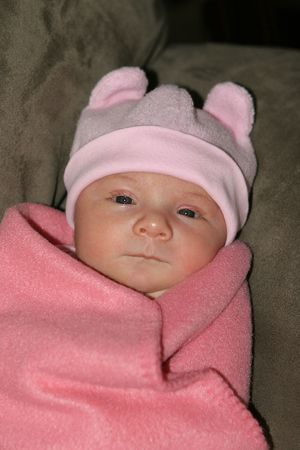 swaddled: Baby girl swaddled in pink blanket with pink cap with ears on head. Stock Photo