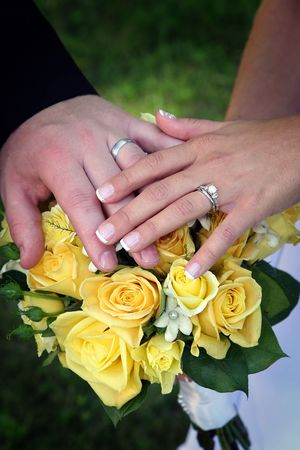 Bride and groom's hands and rings on yellow rose bouquet.