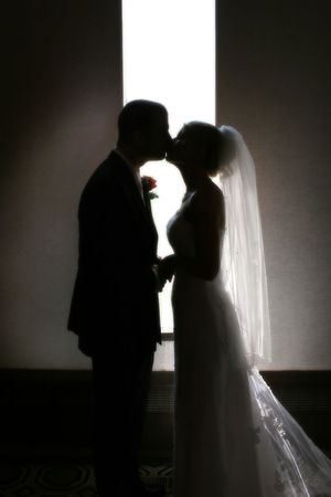 silhouettes of a couple kissing in front of a narrow window Stock Photo - 615046