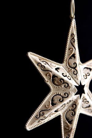angled view: antique metal ornament on black background, angled view Stock Photo