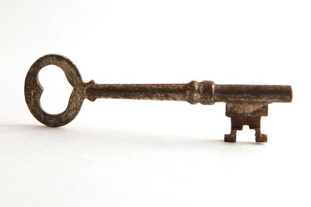 Antique key on white backdrop, teeth right.