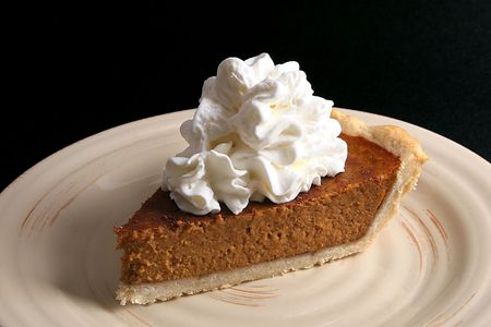 Pumpkin pie with whipped cream from above.
