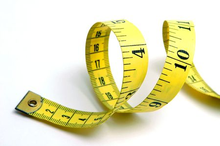 overeat: Close up of curled yellow measuring tape on white background. Stock Photo