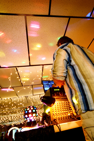 DJ at party with lights on ceiling. photo