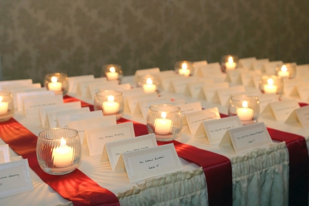 wedding chairs: small candles lighting placecards for guests at a wedding reception
