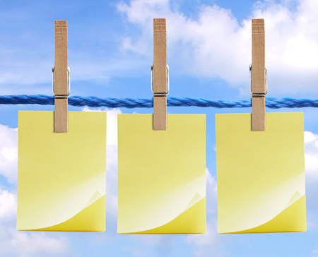 Three adhesive notes held on a line by clothespins under a bright blue sky. Фото со стока