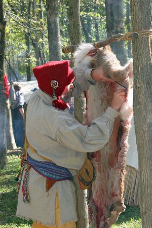 reenact: Man preparing a deer skin