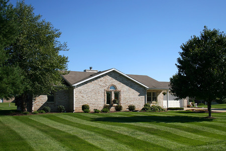 manicured: light brick suburban home with manicured lawn Stock Photo