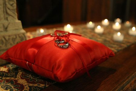 wedding bands tied to a red satin pillow with candles lit in the background. Фото со стока