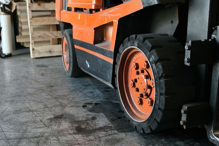 wheels of a pallet truck and warehouse floor with room for text Фото со стока