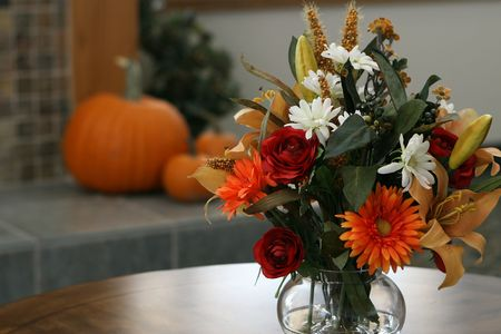 floral arrangement and pumpkins on hearth in an interior setting