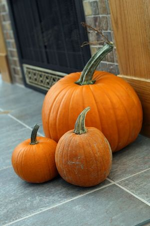 pumpkins on hearth with fireplace in the background