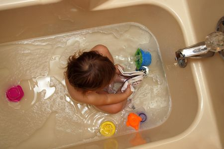supervise: toddler in bathtub with toys from overhead