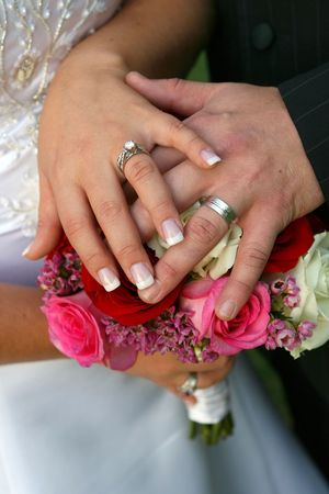 bride and groom's hands on bouquet