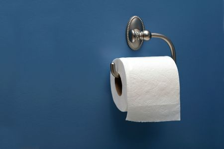 horizontal image of toilet paper on blue wall, right. Фото со стока
