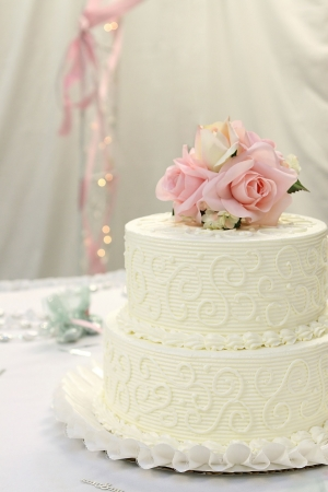 Traditional wedding cake with pink and cream rose cake topper.
