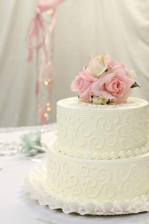 Traditionele bruidstaart met roze roos en room cake topper. Stockfoto