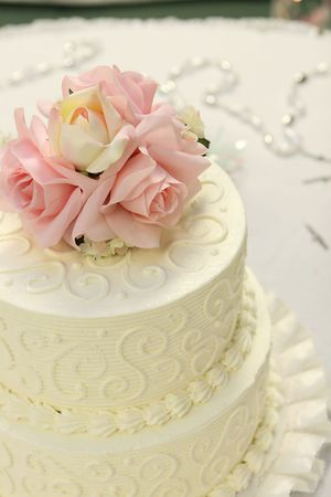 topper: Detail of traditional wedding cake with pink and cream roses. Stock Photo