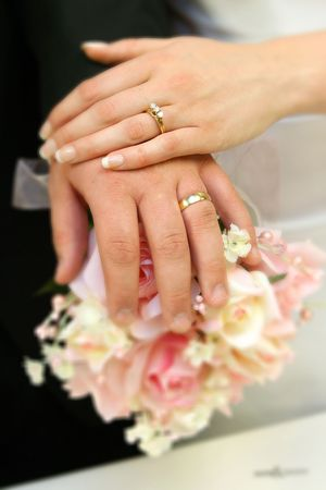 Hands of bride and groom with rings on bouquet.