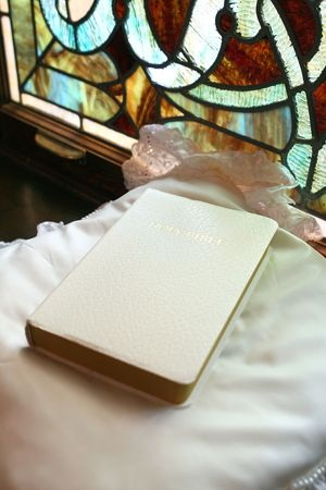 white bible on satin pillow with stained glass in background