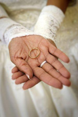 Hispanic bride's hands holding groom's wedding band, shallow dof Фото со стока