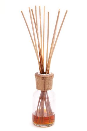 reed diffuser with amber oil on white backdrop