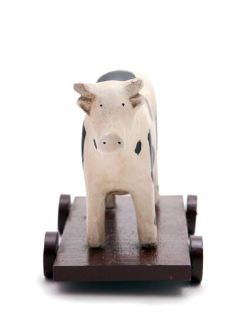 toy cow on wooden base with wheels