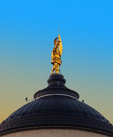 patron: Golden statue of the patron saint on Bergamo cathedral, Italy