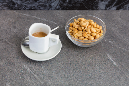 Cup of coffee and roasted nuts on a marble table.