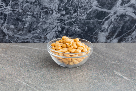 Glass bowl of nuts in closeup on a marble table. Reklamní fotografie