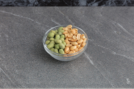 Glass bowl of mixed nuts in closeup on a marble table. 写真素材