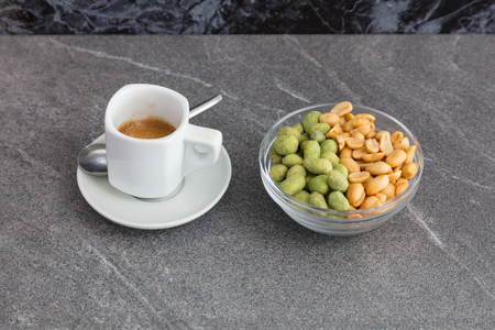 Cup of coffee and roasted mixed nuts on a marble table. Reklamní fotografie