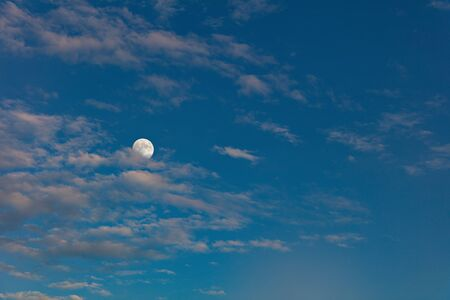 Mysterious evening sky with a full moon. Dramatic clouds in the light of the setting sun.