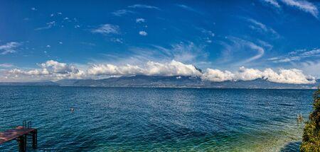 Garda Lake coast on a sunny day with beautiful clouds 写真素材