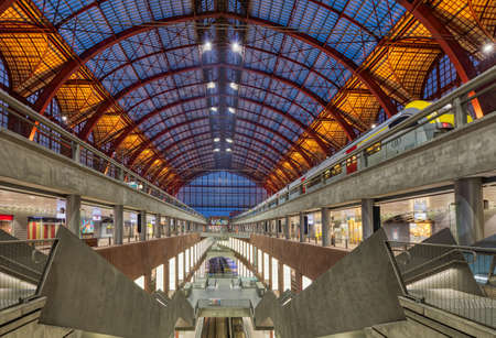 Antwerp, Belgium. Central indoor railway station. Platform made of red metal constructions and panel with departure or arrival schedule. Modern high-speed train.