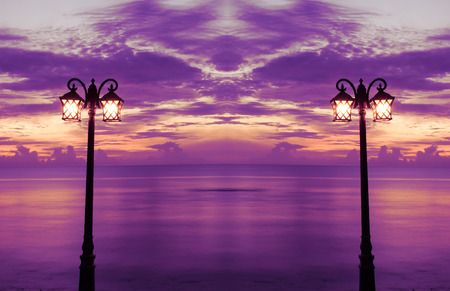 Lamp in the park at the beach and sunrise. Purple and orange. Soft focus.
